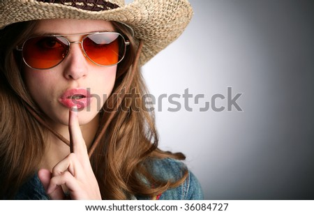 girl in stetson and with finger near lips