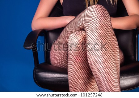 Girl in stockings sitting in a business chair