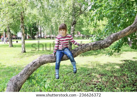 Girl in striped sweater sitting on tree trunk over green grass - stock photo