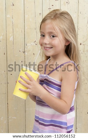 girl in summer dress drinking a soda in a yellow carton cup - stock photo