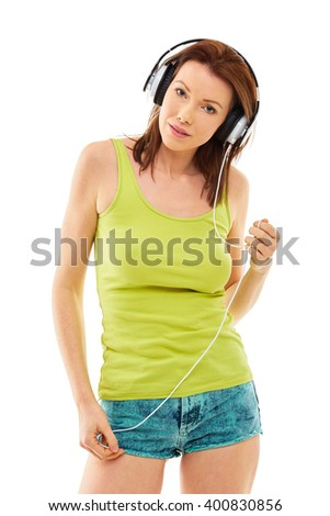 Girl in summer shorts listen to music on her headphones, isolated over white background - stock photo