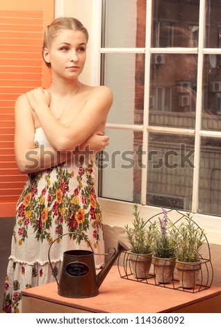 Girl in sundress standing near the window with flowers - stock photo