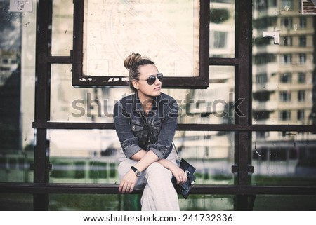 Girl in sunglasses at the bus stop waiting for transport - stock photo