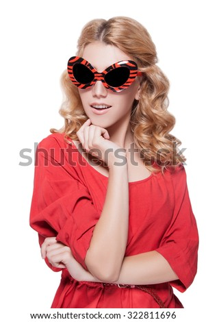 Girl in sunglasses.Blond woman isolated on a white background in a red dress and sunglasses.Cheerful woman with red sunglasses with his mouth open,white teeth.Pretty woman in red  - stock photo