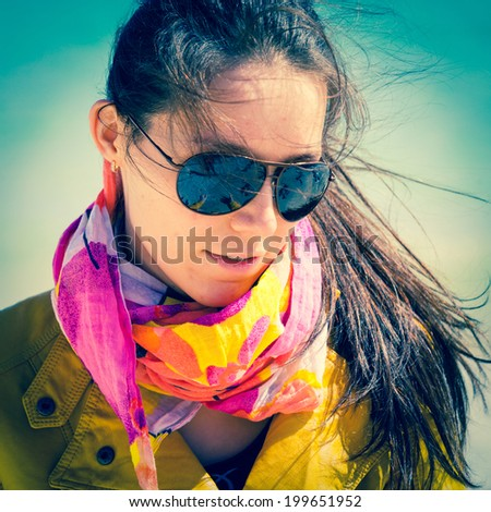 girl in sunglasses with a scarf on a neck