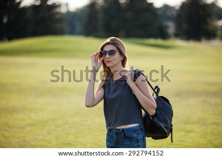 Girl in sunglasses with bag in the park - stock photo