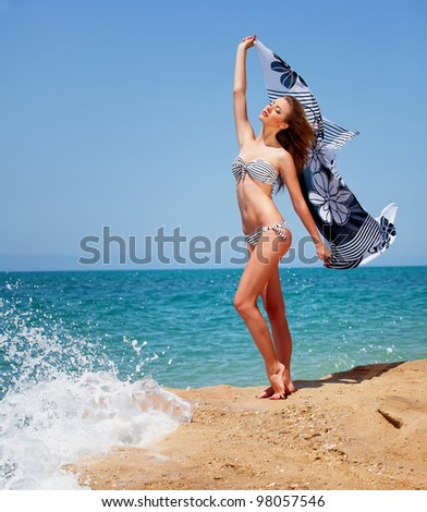 Girl in swimsuit near the sea holding pareo in hands