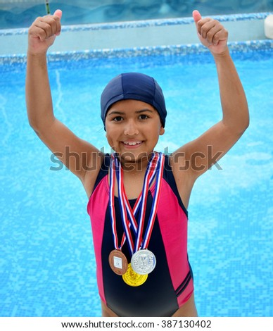 Girl in swimsuit with medals in swimming pool.