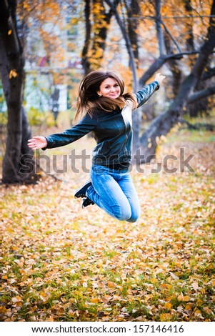 girl in the black jacket jumps in the park in autumn  - stock photo