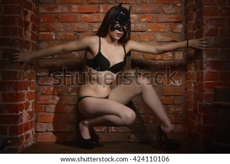 girl in the black mask against brick wall.