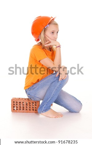 girl in the building helmet sits on a brick