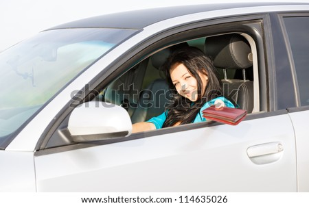 girl in the car gives a driver's license - stock photo