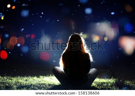 girl in the city at night, illumination, seen from behind - stock photo
