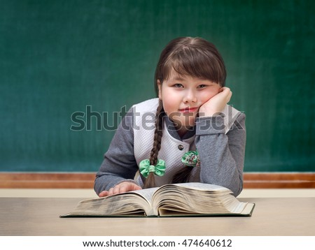 Girl in the classroom daydreaming, smiling. Great tutorial. Blackboard. Child obesity full. Portrait of a schoolgirl.