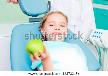 girl in the dentist's chair shows a green apple, regular care of your teeth - stock photo