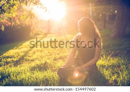 Girl in the garden at golden hour - stock photo