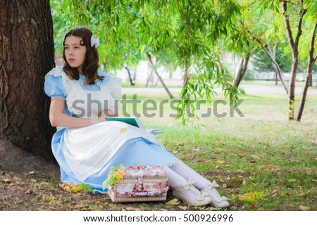 Girl in the image of a character from a fairy tale is sitting under a tree with a book.