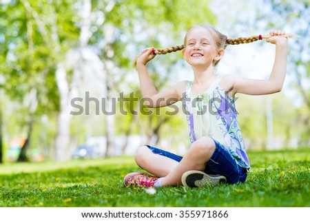 Girl in the park sitting on the grass and keeps himself pigtails - stock photo