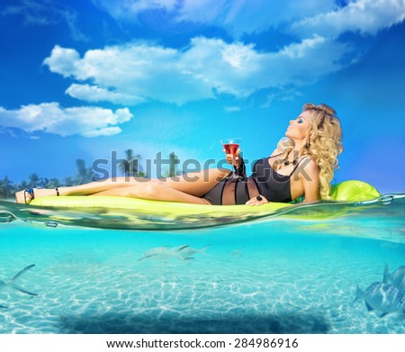 Girl in the sea, on a mattress, with a glass of vermouth - stock photo