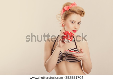 Girl in the style of pin-up posing with a mug in his hands
