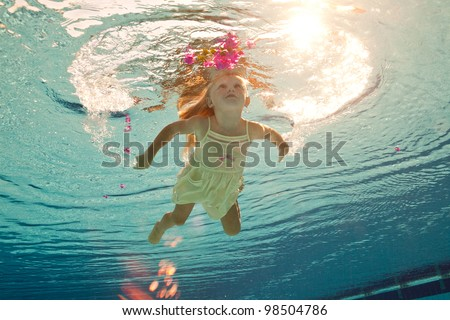girl in the swimming-pool under water with a flower - stock photo