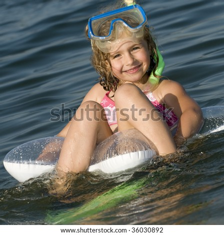 Girl in the water with fins and snorkel - stock photo