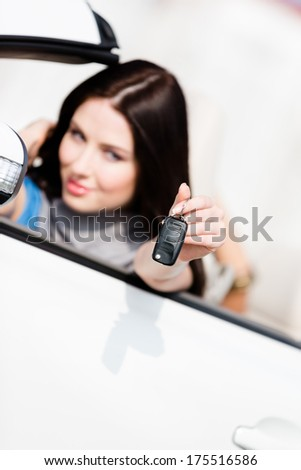 Girl in the white car shows car key. Buying car and getting the freedom - stock photo