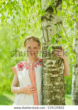 girl in traditional clothes near birch in summer