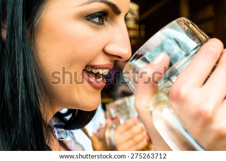 Girl in traditional Dirndl dress, Russian touch but could also be Greek, is drinking beer and having fun at the Oktoberfest - stock photo