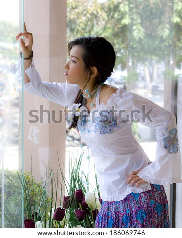 Girl in trendy fashion action. Her hand lean against glass window look forward to someone.window lighting shot.