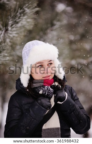 girl in warm hat with ear flaps on the background of snow-covered trees