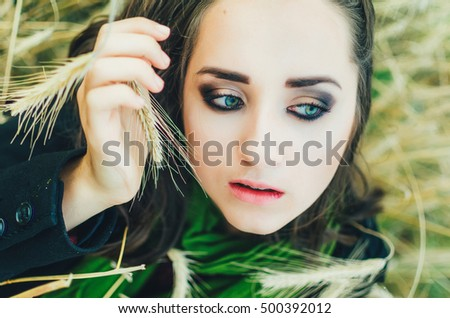 girl in wheat , the ear near the face. autumn , the girl is warmly dressed . she has beautiful blue eyes