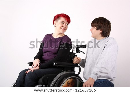 Girl in wheelchair talking with Helper - stock photo