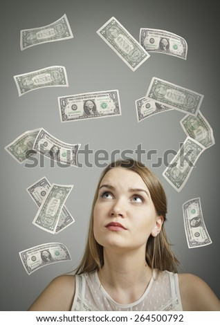 Girl in white and falling dollar banknotes. Currency and lottery concept.