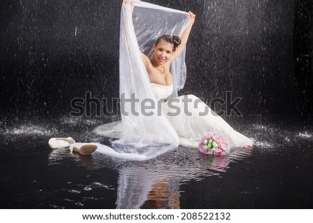 girl in white dress lays in water studio