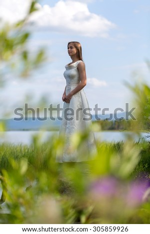 girl in white dress on the lake in the green against the sky - stock photo
