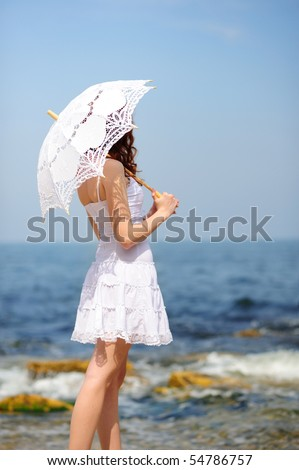 girl in white dress with umbrella on a beach - stock photo