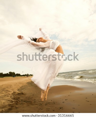 girl in white gown jumping on the seashore