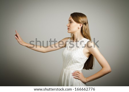 Girl in white is pushing the virtual button. - stock photo