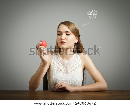 Girl in white is sitting and holding an apple. Doubt or fast food concept. - stock photo