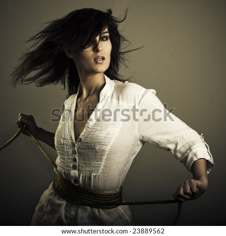 girl in wind with golden rope - stock photo