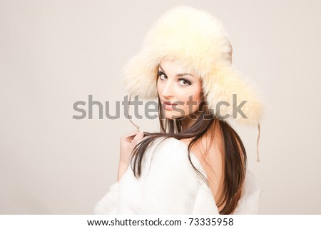 Girl in winter furry hat, isolated studio shot