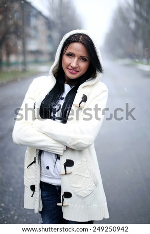girl in winter on the street under the snow - stock photo