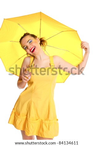 Girl in yellow dress with a yellow umbrella posing on a white background - stock photo