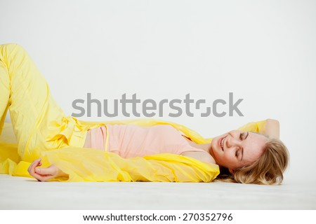 girl in yellow on the floor laughing - stock photo