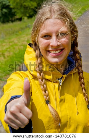 Girl in yellow raincoat with thumb up - stock photo