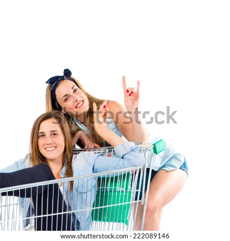 Girl inside supermarket cart with her sister