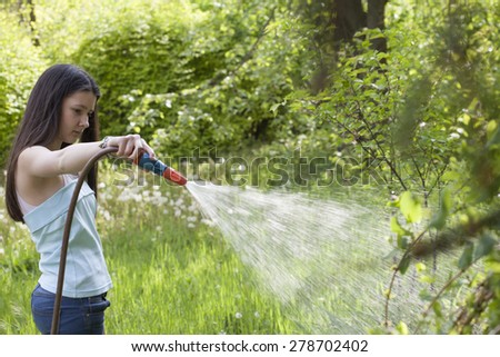 Girl irrigate the grass in the garden  - stock photo