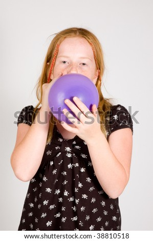 girl is blowing up a balloon on white - stock photo