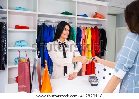 girl is calculated by credit card in a store.Portrait of pretty woman giving credit card to shop assistant while paying for her purchase - stock photo